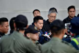 Chan Tong-kai, 20, center, whose case led to plans to change Hong Kong extradition rules, is released and accompanied by Anglican Father Peter Koon Ho-ming at Pik Uk Prison in Hong Kong Oct.23, 2019.