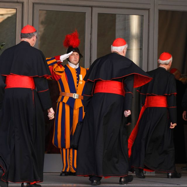 A Swiss Guard salutes as U.S. Cardinals Roger M. Mahony, retired archbishop of Los Angeles, Edward M. Egan, retired archbishop of New York, and Donald W. Wuerl of Washington arrive for the first general congregation meeting in the synod hall at the Vatic an March 4.