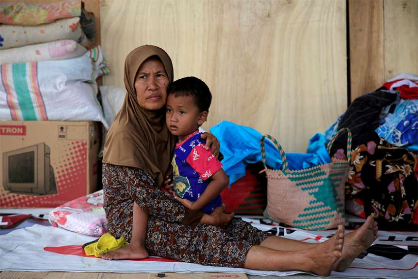 A woman holds her son as they rest Oct. 3 outside their damaged home after an earthquake hit Indonesia's Sulawesi island.