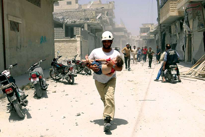 A civil defence member carries an injured girl at a site hit by airstrikes in the rebel-controlled area of Maaret al-Numan, Syria.