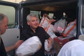 At 7 p.m. at least twice a week, Archbishop Konrad Krajewski pulls up in a large gray van and unloads heavy containers filled with steaming risotto, fresh fruit and drinks for the men, women and children who will soon bed down in the open alley for the night.