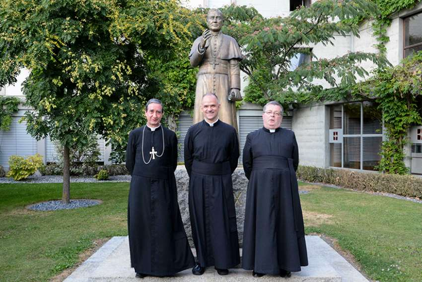 Father Davide Pagliarani, 47, center, was elected July 11 as the new superior general of the traditionalist Society of St. Pius X during the society's general chapter in Econe, Switzerland. Father Pagliarani is pictured after his election with his assistants, Bishop Alfonso de la Galarreta, left, and Father Christian Bouchacourt.