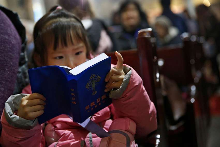 A girl looks at a Bible during Mass in 2016 at a Beijing cathedral. As young people move to cities, Catholic grandparents in rural areas are passing on the faith to their grandchildren.