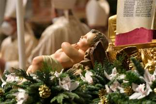 A figurine of the baby Jesus is pictured as Pope Francis celebrates Christmas Eve Mass in St. Peter's Basilica at the Vatican Dec. 24, 2020. The Mass was not open to the general public and began at 7:30 p.m. local time so that the limited number of attendees could return home in time to observe Italy's 10 p.m. curfew.