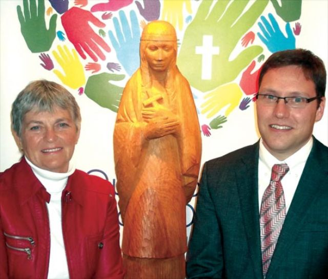 Blessed Kateri Tekakwitha Elementary School principal Paul Gautreau (right) in front of a wood carving of the school's namesake with former teacher Line Douglas who will speak to students during the school's Oct. 22 canonization celebration.