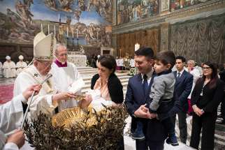 Pope Francis baptizes an infant Jan. 7 in the Vatican's Sistine Chapel.