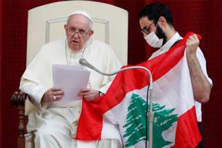 Pope Francis and Maronite Father Georges Briedi hold a Lebanese flag as they pray for the country -- following an explosion in Beirut -- during the the pope's weekly general audience at the Vatican Sept. 2, 2020.