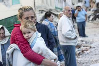 A mother embraces her son in Amatrice, Italy, following an earthquake Aug. 24.