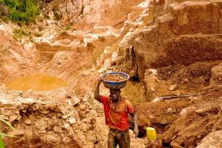 "A Congolese mine worker carries gold rich earth out of a pit for water processing in 2009 in Chudja. Church leaders say telling companies they no longer have to disclose whether their firms use ""conflict minerals"" would be a bad move."
