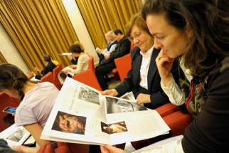 "Women look at a new monthly women's insert called ""Women-Church-World"" in the Vatican's L'Osservatore Romano newspaper this May 30, 2012, file photo. Pope Francis said he would look into New Testament deaconesses."
