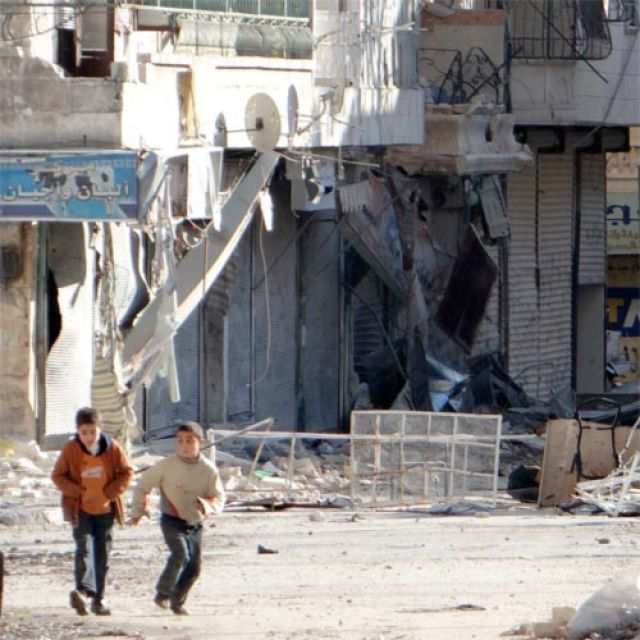 Children run along a street with rubble from buildings damaged by what activists said was a government airstrike in the Aleppo, Syria, Dec. 5. Middle East bishops and patriarchs say the resolution of the Israeli-Palestinian conflict is key to peace throu ghout region.