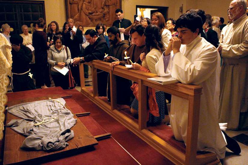Followers of St. Francis pray over a habit Oct. 3 at the Franciscan Monastery of the Holy Land in Washington. Some Franciscans say Pope Francis has spurred a revival of Franciscan spirituality.