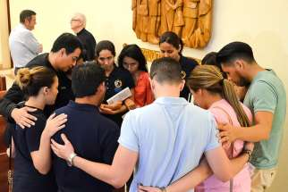 "Father Jorge Torres, director of vocations for the Diocese of Orlando, Fla., prays with young people who participated in the ""Vigil to Dry Tears"" June 13 at St. James Cathedral in Orlando. Father Torres is among the Orlando diocesan priests lending a hand in counseling families and friends of victims of the June 12 massacre at Pulse nightclub in Orlando."