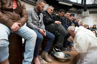 Pope Francis kisses the foot of an inmate during Holy Thursday Mass March 29 at Regina Coeli prison in Rome. The pope celebrated Mass and washed the feet of 12 inmates at the prison.