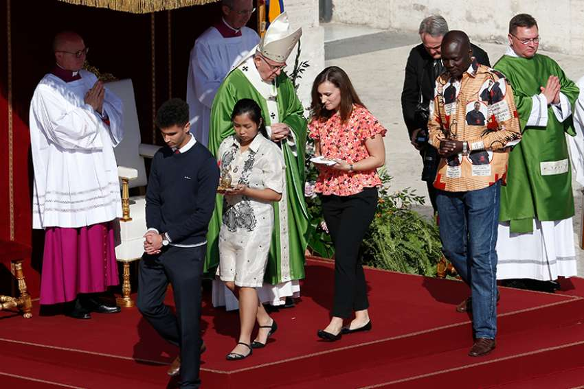 Young people walk away after presenting offertory gifts to Pope Francis during the opening Mass of the Synod of Bishops on young people, the faith and vocational discernment at the Vatican Oct 3. Pictured in red, Emilie Callan is one of Canada's youth observers to the synod.