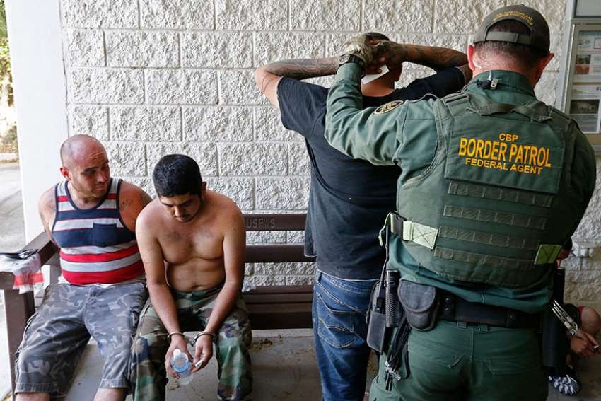 A U.S. Border Patrol agent applies handcuffs to people suspected of crossing the Rio Grande River illegally near McAllen, Texas, Feb. 28.
