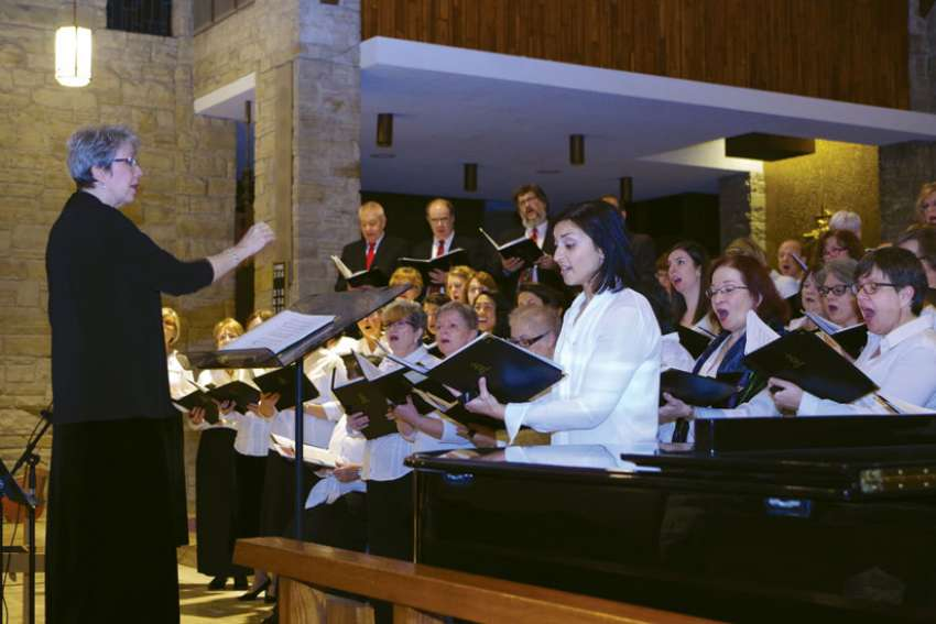 "Staff Arts president and choir director Anne Bolger conducts the group's version of ""O Holy Night"" at the Dec. 2 Christmas concert. Soloist Gilda De Marco Melo is at the right foreground."