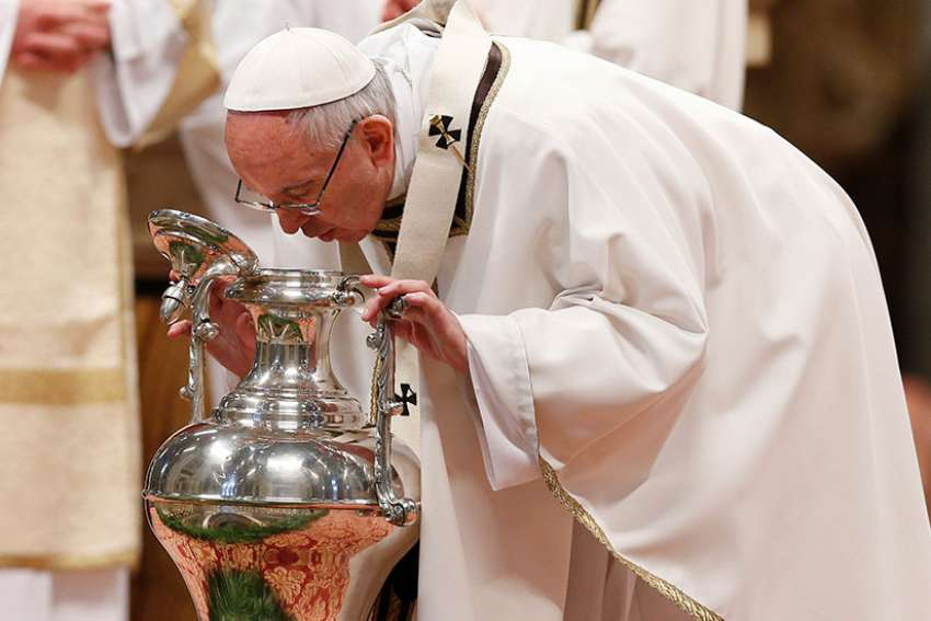 Pope Francis breathes over chrism oil, a gesture symbolizing the infusion of the Holy Spirit, during the Holy Thursday chrism Mass in St. Peter's Basilica at the Vatican April 13.