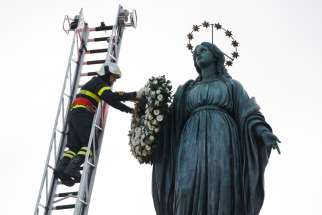 A firefighter places a wreath on a Marian statue overlooking the Spanish Steps in Rome Dec. 8, 2019, the feast of the Immaculate Conception.