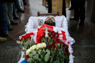 A crucifix and image of Christ are seen in the casket of Georgian Tomaz Sukhiashvili, a member of a self-defense battalion, during his Jan. 21 funeral in Kiev, Ukraine. The United Nations estimated that at least 224 civilians have been killed and another 545 people wounded since mid-January, raising the death toll to more than 5,300 people since April.