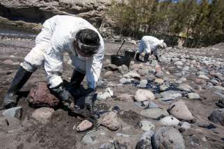 Men collect fuel oil from rocks April 23 following an oil spill along Veneguera beach in Spain's Canary Islands. Few papal encyclicals have been as eagerly awaited as Pope Francis' upcoming statement on the environment to be published June 19.