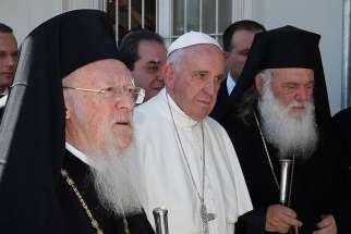 Pope Francis walks with Ecumenical Patriarch Bartholomew of Constantinople, left, and Orthodox Archbishop Ieronymos II of Athens and all of Greece, as they meet refugees at the Moria refugee camp on the island of Lesbos, Greece, April 16. Pope Francis will send high-level observers to the pan-Orthodox council meeting in Crete, beginning June 19, as a sign of respect, support and encouragement of the Orthodox Church.