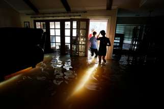 A family that wanted to remain anonymous moves belongings from their home Aug. 31 that was flooded by Tropical Storm Harvey in Houston.