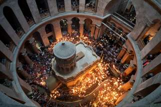 Pilgrims carry candles inside the Edicule, the traditional site of Jesus' burial and resurrection, in the Church of the Holy Sepulcher in the Old City of Jerusalem.