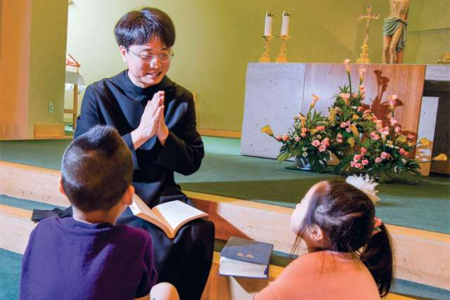 After celebrating Sunday morning Mass at Sacred Heart of Jesus Parish in Korean, Fr. Anselmo Park teaches two children, Aiden Chung and Olivia Yang, about the Catholic faith, just as Park will do after returning to South Korea.