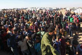 Syrian refugees wait at the border Jan. 13 near Royashed, Jordan. As a donors conference to stem the Syrian refugee crisis opens in London, Syria's neighbors, which have hosted hundreds of thousands of refugees for the past five years, say they cannot continue to bear the brunt of the burden.