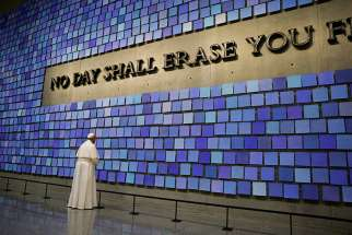"Pope Francis pauses in front of a display at the National 9/11 Memorial and Museum in New York Sept. 25. The Virgil quotation on the wall reads, ""No day shall erase you from the memory of time."""