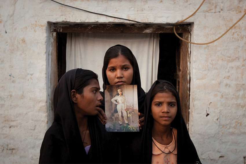 The daughters of Asia Bibi, a Catholic accused of blasphemy, pose in 2010 with an image of their mother while standing outside their residence in Sheikhupura, Pakistan. The Oct. 31 acquittal of Bibi is being challenged in the country's Supreme Court, according to her husband.