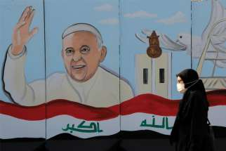 A woman walks past a mural of Pope Francis on a wall surrounding a church in Baghdad Feb. 22. Pope Francis plans to visit Iraq March 5-8.