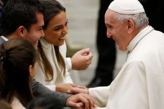 Pope Francis greets a newly married couple during his general audience in Paul VI hall at the Vatican Dec. 11, 2019.