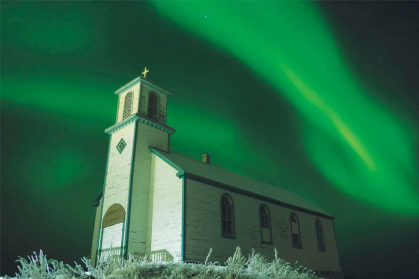 he old Holy Name of Mary Mission in Tsiigehtchic, N.W.T., is bathed in the northern lights. The church is side by side with the new church.