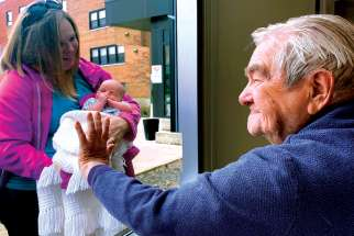 Ed Ecker, 95, meets his newborn great-grandson, Brayden Shantz, through a window at St. Joseph's Lifecare Centre in Brantford, Ont.