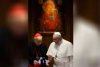 Pope Francis talks with Italian Cardinal Lorenzo Baldisseri, general secretary of the Synod of Bishops, during the morning session on the final day of the extraordinary Synod of Bishops on the family at the Vatican Oct. 18.