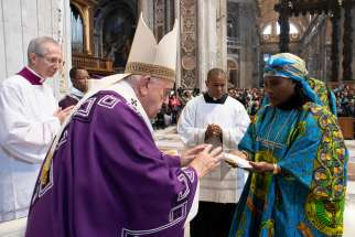 Pope Francis accepts offertory gifts as he celebrates a Mass for the Congolese Catholic community in Rome in St. Peter's Basilica at the Vatican Dec. 1, 2019. The Mass included elements of Congolese culture.