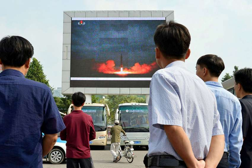North Koreans watch a news report of an intermediate-range ballistic missile launch on a big screen at Pyongyang station in Pyongyang, North Korea, Aug. 30.