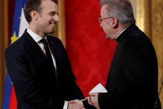 French President Emmanuel Macron greets Italian Archbishop Luigi Ventura as he presents his New Year wishes to members of the diplomatic corps at the Elysee Palace in Paris Jan. 4, 2018. The Vatican said it has lifted diplomatic immunity of the papal nuncio, who has been under investigation in France for allegedly sexually assaulting a city official.