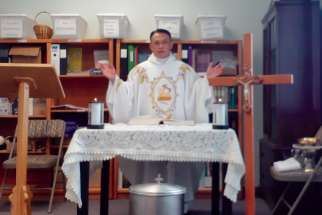 Fr. Mario Infante presides at Mass in the storeroom of his parish office in Brooks, Alta.