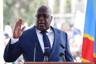 Congolese President Felix Tshisekedi raises his hand as he is sworn into office during his inauguration ceremony in Kinshasa Jan. 24, 2019.
