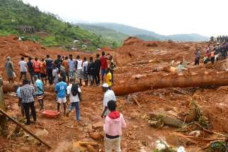 Residents and rescue workers search for survivors after a mudslide in Regent, Sierra Leone Aug. 14.