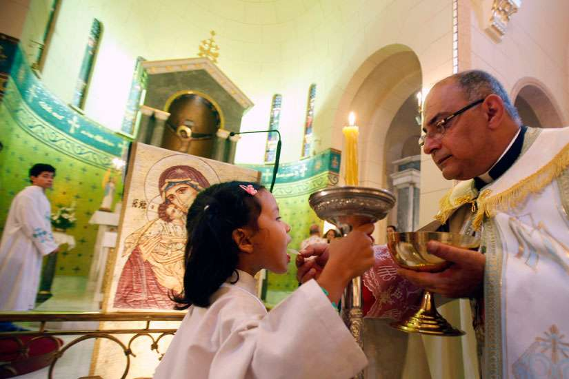 An altar girl receives the Eucharist from a priest.