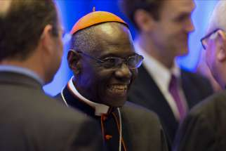 Guinean Cardinal Robert Sarah, prefect of the Congregation for Divine Worship, smiles as he talks with guests at the National Catholic Prayer Breakfast May 17 in Washington.
