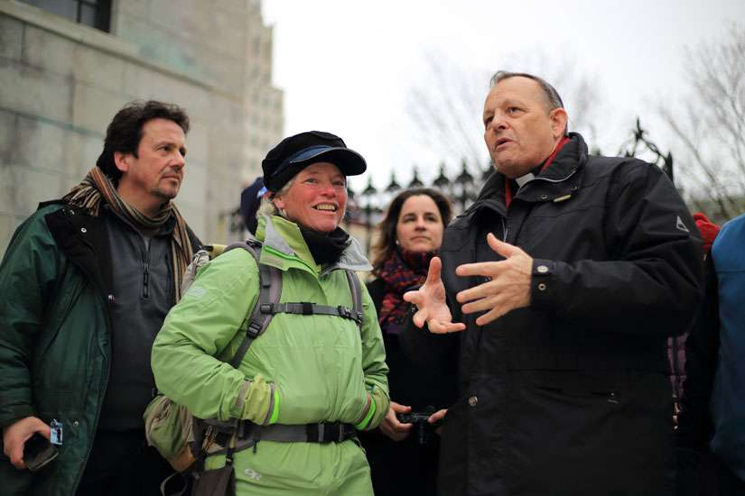 American pilgrim Ann Sieben is greeted outside the Basilica-Cathedral Notre-Dame in Quebec City by its rector, Msgr. Denis Belanger, on Holy Thursday, March 24.