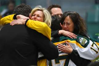 Mourners embrace during an April 8, 2018 vigil at Elgar Petersen Arena in Humboldt, Saskatchewan, to honour members of the Humboldt Broncos junior hockey team who were killed in a fatal bus accident.