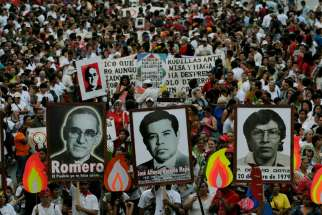 Salvadorans carry a photo of Archbishop Oscar Romero and other victims during a 2008 rally in San Salvador to commemorate the 28th anniversary of their deaths. El Salvador's Supreme Court declared the country's amnesty law unconstitutional; human rights defenders say now restorative justice can bring relief to victims.
