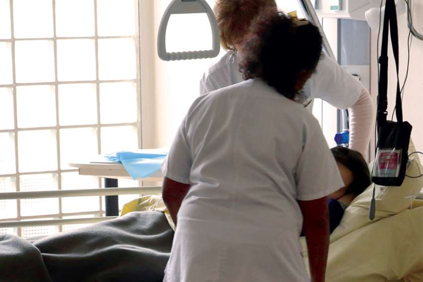 Nurses provide care to a patient at the palliative care unit of a hospital.