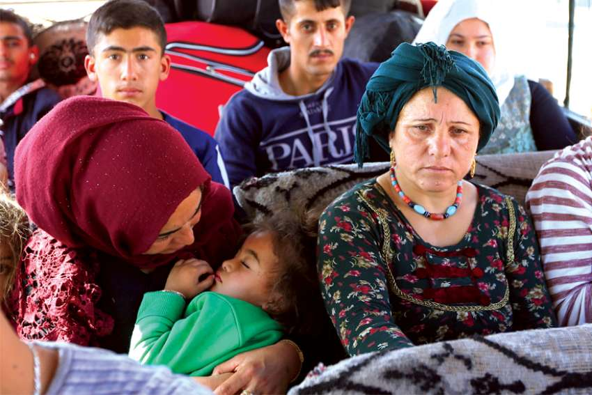 "Displaced Syrian families, who fled violence after the Turkish offensive against Syria, sit in a bus on their way to camps in the Iraqi province of Dahuk Oct. 16, 2019. In an Oct. 17 plea, Archbishop Timothy P. Broglio of the U.S. Archdiocese of the Military Services, chairman of the U.S. bishops' Committee on International Justice and Peace, urged countries choose ""dialogue over confrontation"" to resolve their differences."